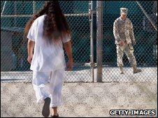 Detainee and soldier walk past each at other at the camp