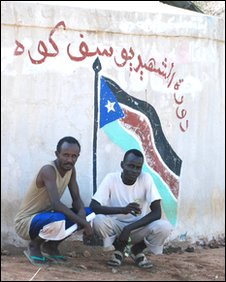 Men in Sudan's Nuba mountains pose by a wall painting of the southern Sudanese flag and a slogan in support of the south's ruling SPLM party