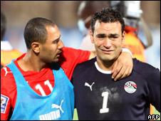Egypt's Mohammed Shawki (L) comforts goalkeeper Essam al-Hadary (R)