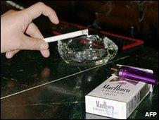 A smoker flicks ash in an ashtray