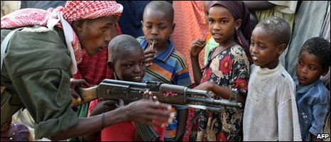 A Somali government soldier in Mogadishu shows children a Kalashnikov rifle, file image