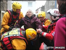 Firefighters and RNLI personnell rescue Pat Edwards, aged 81, from her home in the centre of Cockermouth