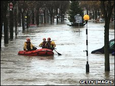 Rescue workers search Cockermouth High Street in a boat on Friday morning