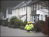 Rescue workers walk down a flooded street