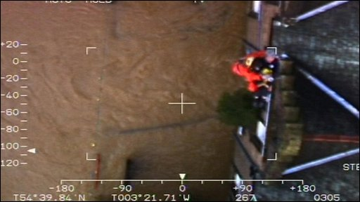 RAF rescue crew winching man out of house