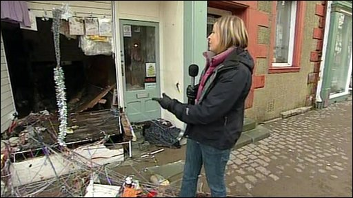 The BBC's Nicola Pearson outside a damaged shop in Cockermouth,