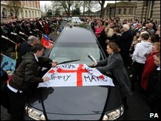 A flag and flowers are laid on the hearse