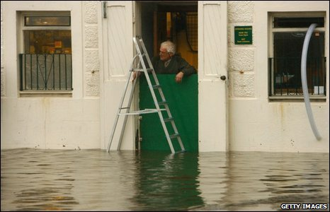 A Dumfries business owner looks out on the floods