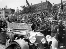 Adolf Hitler (l) standing in a convertible Mercedes reviewing troops in 1937