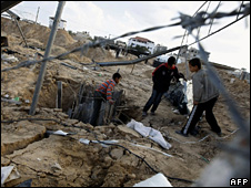 Children inspect damage caused by an Israeli air strike on a smuggling tunnel near Rafah (24 November 2009)