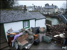 Debris lies outside a house next to the river Cocker in Cockermouth town centre following the recent floods