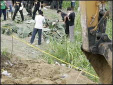 Police inspect the bodies in hillside grave in Ampatuan, Maguindanao province
