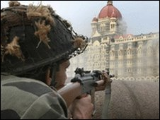 An Indian soldier aims his rifle outside the Taj Mahal hotel in Mumbai, 29 November