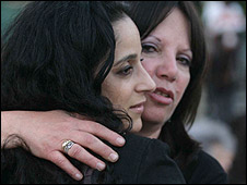 Yehudit Rosenberg (r) hugs a member of the Chabad community in the wake of the attack