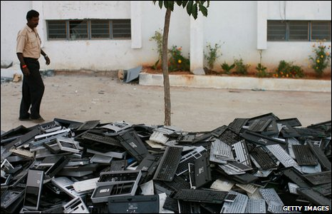 A man walks past a pile of computer keyboards