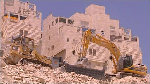 Diggers moving building rubble on an Israeli settlement