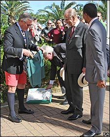 Duke of Edinburgh being given green shorts