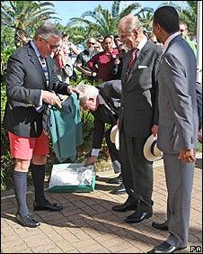Duke of Edinburgh being given green shorts