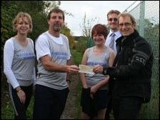 Members of the Maiden Newton running club present Peter Henshaw with a cheque