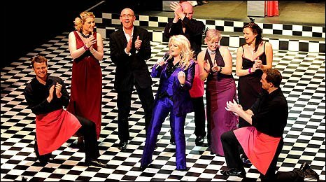 Image shows Bonnie Tyler singing the title song at the opening night of The Cappuccino Girls at the Grand Theatre in Swansea with actors and Mal Pope
