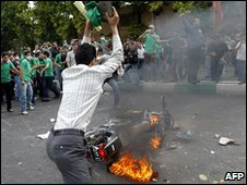 Man throwing a stone at a burning police motorbike (13/06)