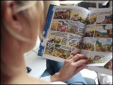 A person poses reading Asterix last comic book by late writer Rene Goscinny and illustrator Albert Uderzo