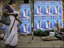 A woman walks past posters of Sri Lankan President Mahinda Rajapaksa in Colombo on Tuesday, Nov 24, 2009