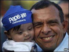 Porfirio Lobo carries a child on electio day in Honduras