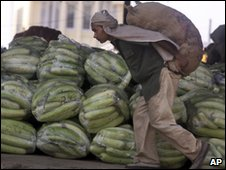 An Indian worker unloads vegetables