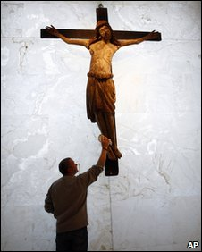 A man polishes an Italian painted wood crucifix from a church around 1250,