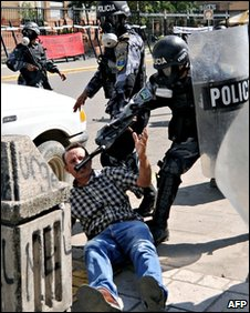 Riot police clash with a protester in the Honduran city of San Pedro Sula