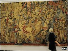 "A woman walks past ""The War of Troy"" tapestry made in Tournai, Belgium between 1460 and 1490"