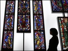 Woman looks at a display of a 13th-century French stained glass windows