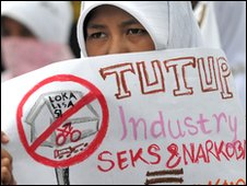 An Indonesian Muslim protester holds a placard during an AIDS/HIV campaign in Jakarta