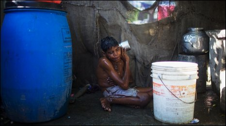Sachin Kumar, 15, who was born with a birth defect, is seen here washing at his home in a slum near the deserted Union Carbide factory on November 30, 2009