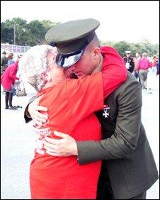 A marine receives a hug at graduation