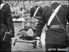 Man being taken off the pitch on a stretcher
