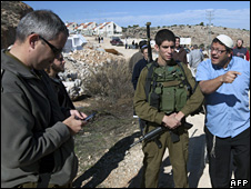 Israeli settler argues with soldier