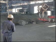 HEG worker lifting graphite electrodes