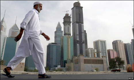 A man walks in front of the Dubai skyline