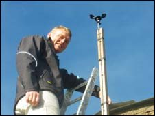 Tom Heap on ladder to check wind meter