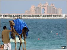 A man stands by his camel at the beach opposite the Atlantis Hotel in Dubai