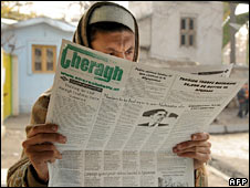 An Afghan man reads a newspaper featuring an image of Mr Obama in Kabul. Photo: 2 December 2009