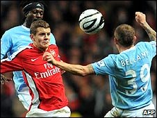 Arsenal's Jack Wilshere battles for the ball with Man City's Craig Bellamy