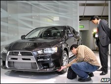 A customer checks a tyre on a Mitsubishi car