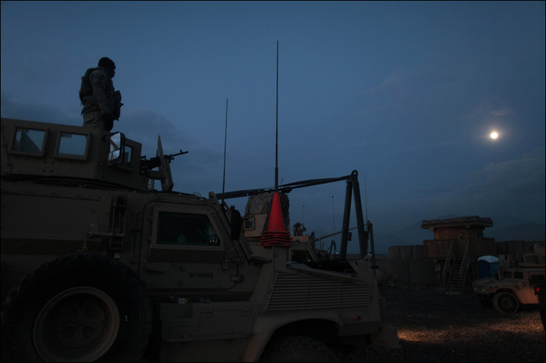 A soldier belonging to a route clearance team stands atop a vehicle as day breaks at Forward Operating Base Airborne