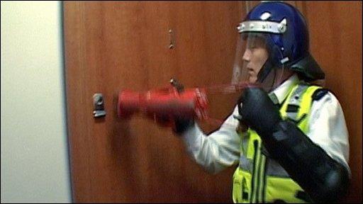 Police officer forcing door
