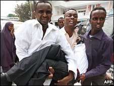 An injured man is carried away in Mogadishu, Somalia (3 Dec 2009)