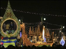 A float passes a giant portrait of King Bhumibol Adulyadej and Queen Sirikit during parade in Bangkok - 3 December 2009