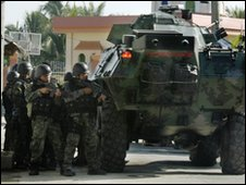 Soldiers raid Ampatuan family compound in the Philippines under cover of armoured vehicle, 4 December 2009